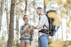 Укомплектуйте личным составом утихомиривать его умоляющую женщину после быть потерянным в лесе с рюкзаками стоковое фото