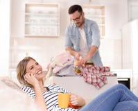 Укомплектуйте личным составом утюжить пока женщина отдыхая и говоря на телефоне Стоковое Изображение