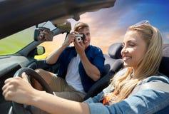 Укомплектуйте личным составом фотографировать женщину управляя автомобилем камерой фильма Стоковое Изображение RF
