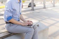 Укомплектуйте личным составом фрилансера бизнесмена работая на его компьтер-книжке outdoors Стоковое фото RF