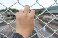 Укомплектуйте личным составом хватку бар клетки с defocus предпосылки города Стоковые Фотографии RF