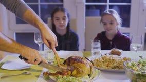 Укомплектуйте личным составом цыпленка отрезков на праздничной таблице и положите бедренную кость цыпленка на плиту ` s дочери сток-видео