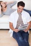 Укомплектуйте личным составом читать новости пока его подружка слушает к нот Стоковые Изображения RF