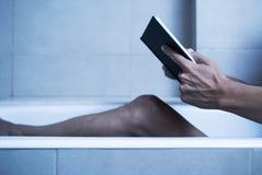Укомплектуйте личным составом чтение в ванне в загадочной атмосфере стоковые изображения