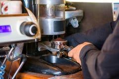 Укомплектуйте личным составом Barista делая порошок кофе меля на машине кофе Стоковая Фотография