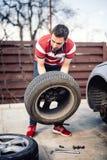 Укомплектуйте личным составом chaning колесо на стороне дороги, детали спущенной шины стоковая фотография rf