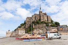 Укомплектуйте личным составом prepairing его шлюпка на пляже около Святого Мишеля Mont Стоковое фото RF