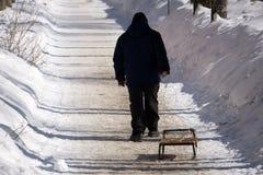 Укомплектуйте личным составом puling ловкости вверх по снежной горе на зимний день стоковое изображение rf