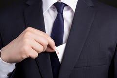 Укомплектовывает личным составом карточку туза руки пряча в карманн костюма Стоковая Фотография RF
