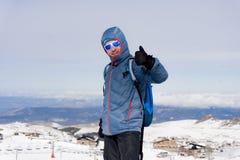 Укомплектуйте личным составом давать большой палец руки вверх после достижения пикового саммита trekking в горе снега стоковая фотография