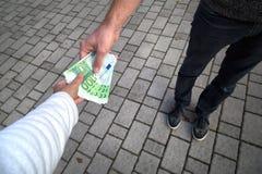 Укомплектуйте личным составом давать евро банкнот в руке женщины Стоковая Фотография RF
