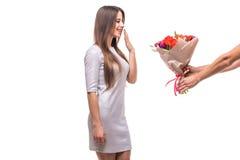 Укомплектуйте личным составом давать пук изолированных цветков и удивленной женщины Стоковая Фотография