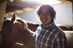 Укомплектуйте личным составом ласкать коричневую лошадь в конюшне стоковое изображение rf