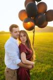 Укомплектуйте личным составом дал девушке воздушные шары в дне ` s валентинки и обняло ее Стоковая Фотография