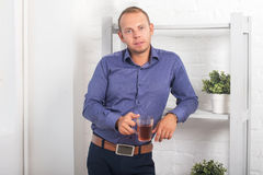 Укомплектуйте личным составом бизнесмена стоя в офисе с полок с кружкой чая Стоковые Фотографии RF