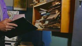 Укомплектуйте личным составом бумагу касаний клерка учитывая ретро в старом офисе видеоматериал
