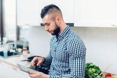 Укомплектуйте личным составом варить в новой кухне, используя таблетку для рецептов и смотреть на интернете Стоковое Изображение