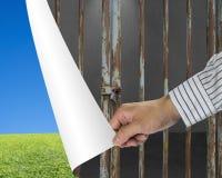 Укомплектуйте личным составом дверь стальных прутов изменения запертую к зеленой сини луга и ясности Стоковые Изображения RF
