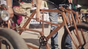 Укомплектуйте личным составом велосипед металла стойки золотой в линии с другим различным на улице выставка swallowtail лета трав сток-видео