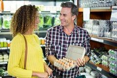 Укомплектуйте личным составом взаимодействовать с женщиной пока держащ коробку яичка стоковое изображение rf