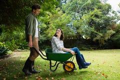 Укомплектуйте личным составом взаимодействовать с женщиной пока нажимающ тачку в саде стоковые изображения