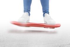 Укомплектуйте личным составом двигать дальше красный цвет завишите изолированный самокат доски Стоковое Изображение RF