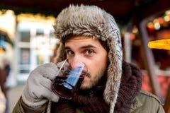 Укомплектуйте личным составом вино кефали питья теплое на рождественской ярмарке Стоковая Фотография RF