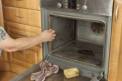 Укомплектуйте личным составом вставать на поле в кухне и очищает печь Стоковая Фотография