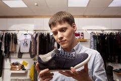 Укомплектуйте личным составом выбирать ботинки во время покупок обуви на обувном магазине Стоковое Фото