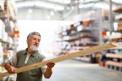 Укомплектуйте личным составом выбирая и покупая древесину конструкции в магазине DIY Стоковые Фотографии RF