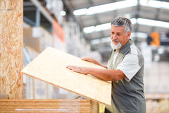 Укомплектуйте личным составом выбирая и покупая древесину конструкции в магазине DIY Стоковое Изображение RF