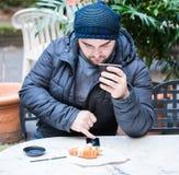 Укомплектуйте личным составом выпивать чашку кофе и проверять социальные средства массовой информации стоковое изображение
