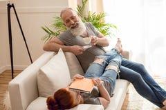 Укомплектуйте личным составом выпивая кофе и жену используя таблетку пока тратящ время совместно Стоковое Изображение RF