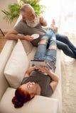 Укомплектуйте личным составом выпивая кофе и жену используя таблетку пока тратящ время совместно Стоковая Фотография