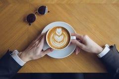 Укомплектуйте личным составом выпивая кофе на таблице в утре Стоковые Изображения RF