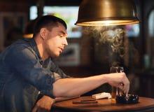 Укомплектуйте личным составом выпивая пиво и куря сигарету на баре Стоковая Фотография RF
