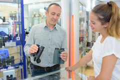 Укомплектуйте личным составом в магазине держа 2 бинокля пар Стоковое Фото
