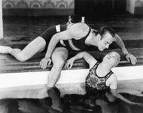 Укомплектуйте личным составом гнуть сверх для того чтобы расцеловать женщину в бассейне (все показанные люди более длинные живущи Стоковые Изображения RF