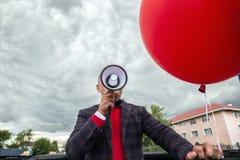 Укомплектуйте личным составом говорить над мегафоном по мере того как он делает систему оповещения, участвует в протесте или орга стоковые фотографии rf