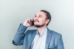 Укомплектуйте личным составом говорить на телефоне, посмотрите вверх и усмехнитесь Бизнесмен счастливый о хороших новостях Стоковое Изображение RF