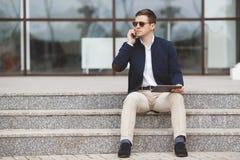 Укомплектуйте личным составом говорить на телефоне сидя на лестницах стоковое изображение rf