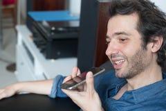Укомплектуйте личным составом говорить на телефоне с ассистентом цифрового голоса стоковые изображения
