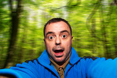 Укомплектуйте личным составом говоря selfie вытягивая смешную сторону на запачканной предпосылке Стоковое Изображение RF