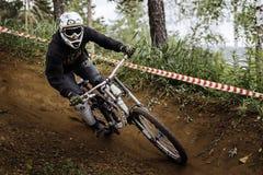 укомплектуйте личным составом гору спортсмена велосипед вокруг острого поворота в лесе Стоковое Изображение RF