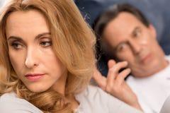 Укомплектуйте личным составом лежать в кровати и касающих волосах женщины осадки постаретой серединой Стоковые Изображения