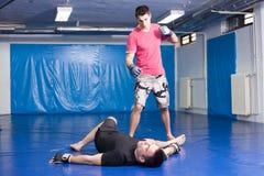 Укомплектуйте личным составом лежать на голубых циновках во время тренировки коробки Стоковое Изображение