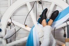 Укомплектуйте личным составом лежа вверх ногами нося белые джинсы и черные ботинки Стоковые Изображения RF