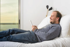 Укомплектуйте личным составом лежа кровать усмехаясь держащ заход солнца захода солнца таблетки через окно Стоковая Фотография