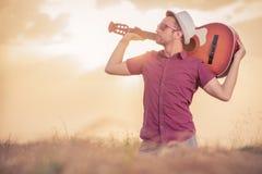 Укомплектуйте личным составом держать акустическую гитару за его шеей outdoors стоковая фотография