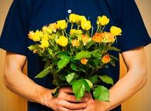 Укомплектуйте личным составом держать букет желтых и оранжевых роз День Women s, Va Стоковые Изображения